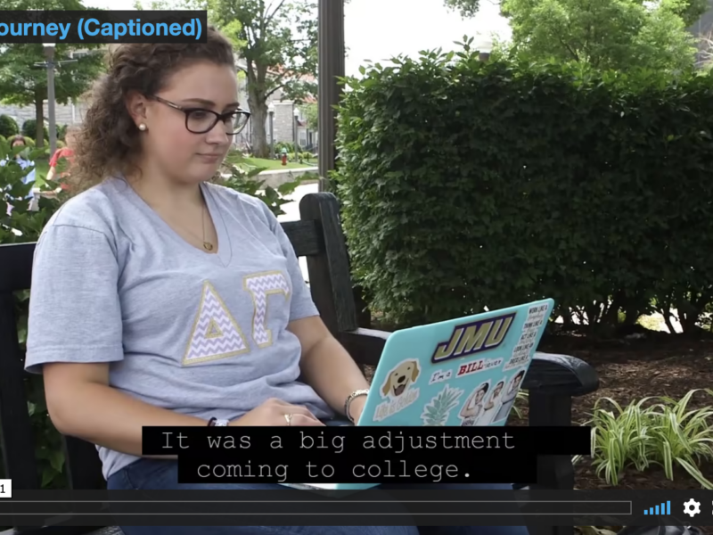 Video capture: Annie sits outside on a bench, her laptop open.