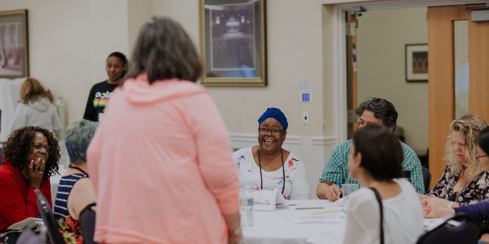 parents sit around a table at an event talking and laughing