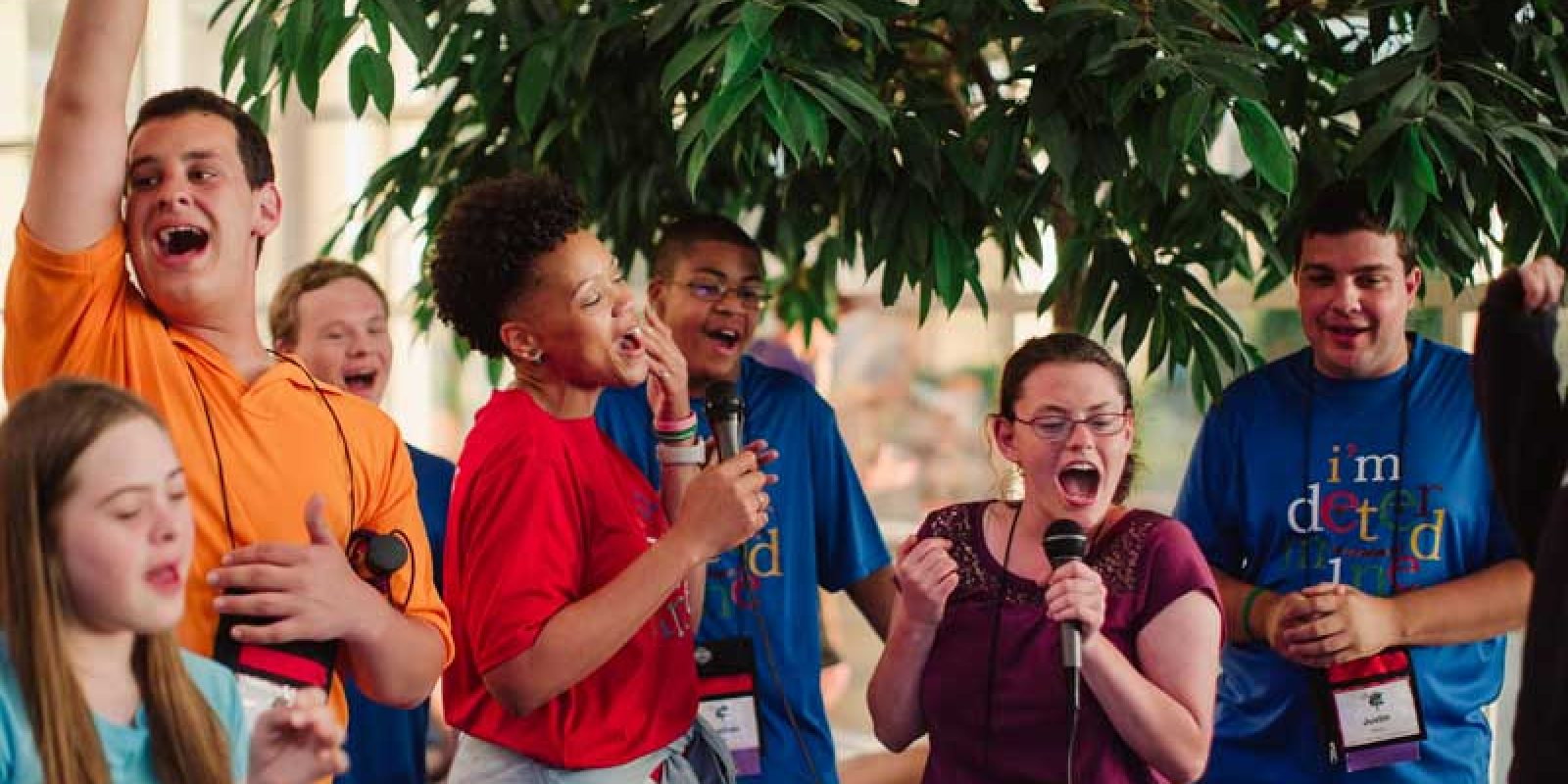 youth leaders in brightly colored shirts sing joyfully into microphones